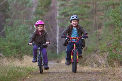 Children riding bikes, Inshriach Forest, Cairngorms National Park, Scotland.