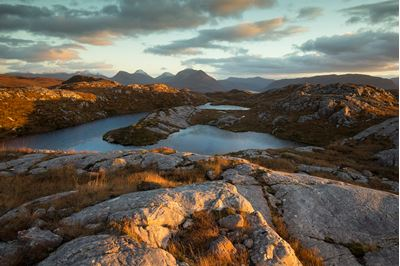 Late evening light across remote hill lochan, Wester Alligin, Wester Ross, Scotland.